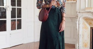 Floral top tucked into jewel tone midi skirt with tall boots