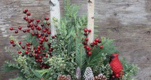 winter urn arrangement with pinecones, red berries and cardinals
