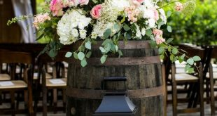 Beautiful floral arrangement on top of barrel with large lanterns at the entranc...